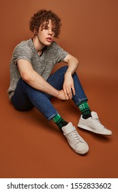 """Full shot of a curly haired man in blue jeans, gray tee, gray sneakers and black socks with green stripes and lettering """"1997, hip-hop, fuck off"""". The man is posing on the brown background."""