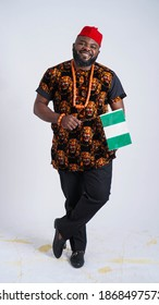 Full shot of a handsome Nigerian Igbo man carrying the Nigerian Flag