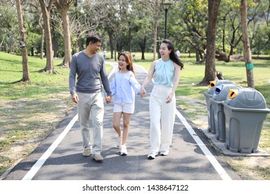 full shot of happy asian family, parents and children are resting by walking and running in the park during summer season with green trees