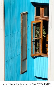 Full shot of open vertical window of old wood next to a wall saturated with calypso color