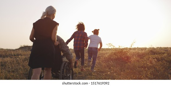 Full shot of a soldier and his family walking on a meadow then hugging
