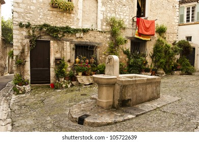 Full shot of a water fountain in a quaint Saint-Paul-de-Vence village.