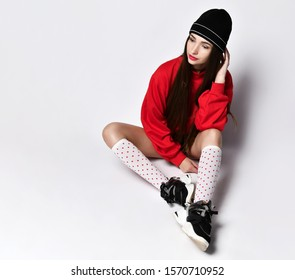 full shot of a young European brunette girl in short black shorts, a red hoodie, fashionable sneakers and white red polka dot socks. Sitting in a free pose on a light floor