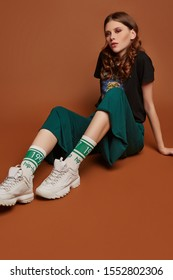 """Full shot of a young European girl in wide green trousers, t-shirt with heavy metal band name, white sneakers and white socks with green stripes and lettering """"1997, hip-hop, fuck off""""."""