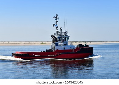 Full side view of bright red modern tugboat in Rotterdam harbor against backdrop of the beach and clear blue sky