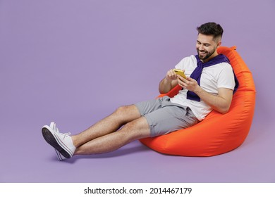 Full size body length attractive smiling young brunet man 20s wear white t-shirt purple shirt sit in bag chair hold in hand use mobile cell phone isolated on pastel violet background studio portrait - Shutterstock ID 2014467179
