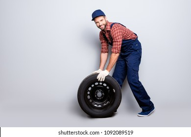 Full size body portrait with copy space of joyful attractive mechanic with stubble in blue overall, shirt, cap trundle tire looking at camera, isolated on grey background
