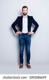 Full size body portrait of elegant attractive teacher with stubble holding two arms on waist looking at camera isolated on grey background, wearing jacket jeans shirt