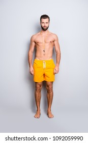 Full size body portrait of fit sportive lifeguard with stubble in yellow shorts isolated over grey background, looking at camera