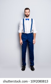 Full size full body portrait of handsome attractive singer in blue ourfit, wearing bowtie, white shirt, suspenders, isolated over grey background