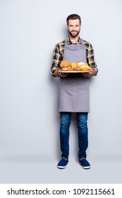 Full size body portrait of joyful cheerful baker in jeans, shoes, shirt, apron with stubble having, showing tray with bakery products, looking at camera, isolated on grey background
