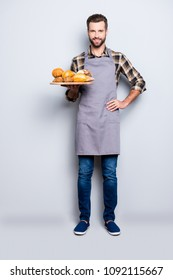 Full size body portrait of positive attractive baker in jeans, shoes, shirt, apron with stubble having tray with bakery products, looking at camera, isolated on grey background
