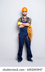 Full size body portrait of virile brutal electrician with bristle in overall, shirt, holding rolled cable in hand, having his arms crossed, looking at camera, isolated on grey background