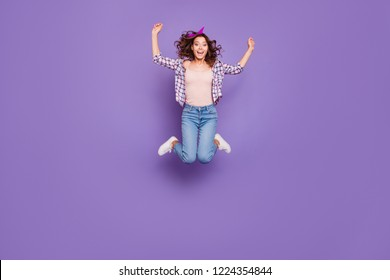 Full size charming lovely cute sweet gorgeous nice positive lady with her brunette curly hairstyle she wear in denim casual jeans raised hands up jump isolated on vivid violet background
