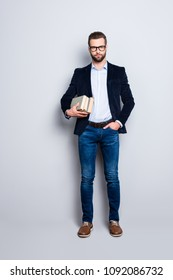 Full size fullbody portrait of attractive stylish teacher in shirt, jacket, jeans with stubble having three books, holding hand in pocket, looking at camera isolated on grey background