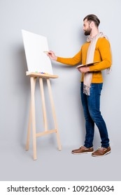 Full size fullbody portrait of busy creative artist with scarf around neck, hairstyle, in jeans, sweater, holding colorful palette and drawing a picture, isolated on grey background
