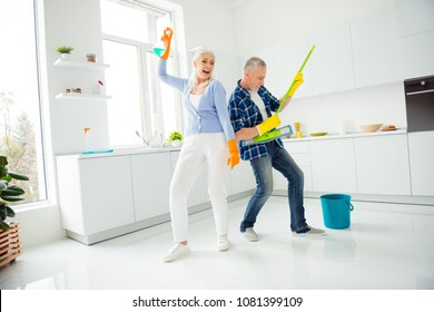 Full size, fullbody portrait of crazy foolish funny mad cool couple of senior dancing, singing, man playing on mop like guitar, woman holding spray in raised hand, positive people concept
