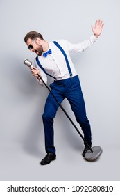 Full size fullbody portrait of famous creative singer in blue pants with suspenders, black glasses, singing hit with open mouth in mic gesture with hand isolated on grey background