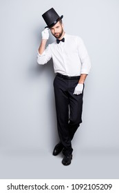 Full size fullbody portrait of stylish attractive magician in tophat, formal wear,  looking at camera, staying leg by foot, holding hat with hand, isolated on grey background