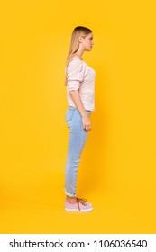 Full size fullbody profile side view portrait of charming pretty girl wearing pants shoes isolated on bright vivid yellow background