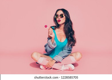 Full size leisure lifestyle rest relax dreamy attractive lady style denim jeans shirt with her ideal curly hairstyle she sit on floor isolated on bright pastel pink background hold sweet sucker stick