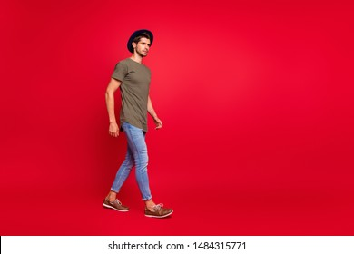 Full size photo of amazing guy walking park wear casual outfit isolated on red background