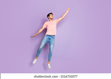 Full size photo of amazing guy jumping and flying high with imaginary umbrella wear casual outfit isolated on purple color background