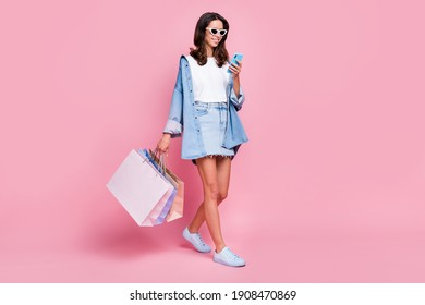 Full size photo of brunette beautiful girl wear short denim skirt jacket glasses hold bags phone isolated on pink color background