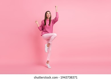 Full size photo of brunette optimistic girl fists wear pink sweater pants sneakers isolated on crimson background