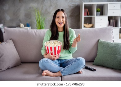 Full size photo of charming candid girl asian have free time sit divan legs bare foot crossed watch funny series eat pop corn box laughing in house indoors