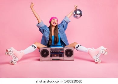 Full size photo of charming girl holding glittering disco ball feeling rejoice raising hands wearing body-suit socks isolated over pink background