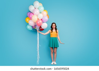 Full size photo of cheerful candid lovely girl hold many air balloons enjoy party celebration wear good look short mini clothes singlet footwear isolated blue color background
