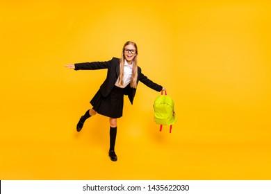 Full size photo of cheerful child wear eyeglasses eyewear raising leg isolated over yellow background