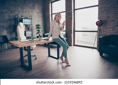 Full size photo of confident focused middle aged leader business woman sit on wooden table in office use her smartphone chat with her clients workstation partners wear high-heels