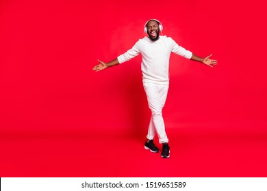 Full size photo of cool dark skin man listening favorite playlist in earflaps enjoy best moment moving with rhythm wear knitted sweater and trousers isolated red background