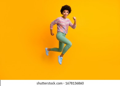 Full size photo of crazy dark skin curly lady jumping high rush fast discount shopping black friday low prices wear colorful pullover green pants shoes isolated yellow color background