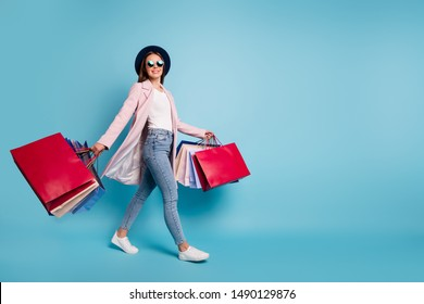 Full size photo of cute pretty cheerful lady in eyeglasses eyewear go shopping for bargains wear season cote denim jeans isolated over blue background