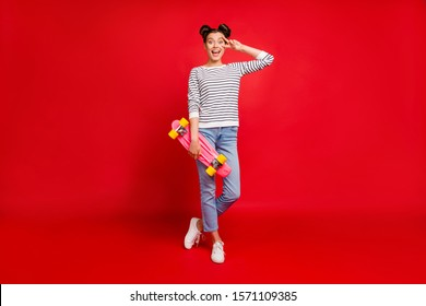 Full size photo of cute teen girl have sportive weekends hold pink skateboard make v-signs feel content expression wear white denim jeans outfit sneakers isolated red color background
