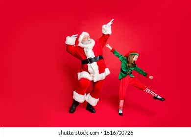 Full size photo of excited santa claus and elf in hat with eyeglasses eyewear dancing fooling wearing bright costumes isolated over red background
