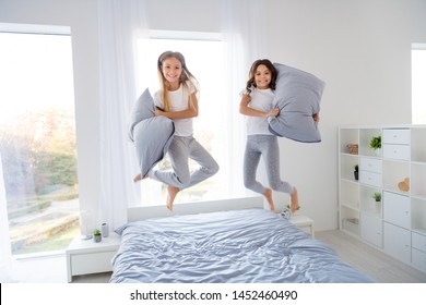 Full size photo of funny children hold hand pillows jumping bed room indoors
