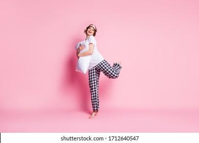 Full size photo of funny crazy lady hold hug pillow raise one leg good morning mood wear sleep mask white t-shirt checkered pajama pants barefoot isolated pink color background