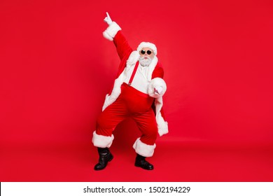 Full size photo of funny fat overweight santa claus with big abdomen in eyewear dance raise hand wear style stylish trendy trousers pants isolated over red background