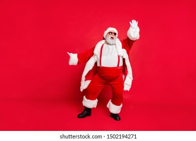Full size photo of funny fat overweight santa claus with big abdomen raise his arm dance wear style stylish trendy eyeglasses eyewear pants trousers isolated over red background