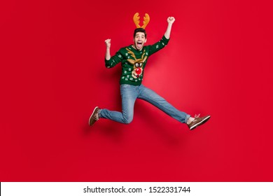 Full size photo of funny guy jumping high running to x-mas free shopping wildly shouting wear pullover with ugly deer ornament isolated red color background