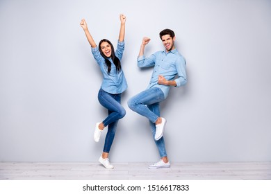 Full size photo of guy and lady celebrating successful business project raising fists air wear casual jeans clothes isolated grey color background