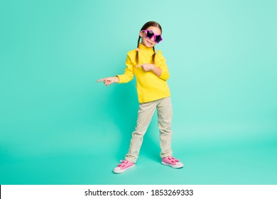 Full size photo of happy positive brown haired girl point empty space wear white pants yellow turtleneck isolated on teal color background
