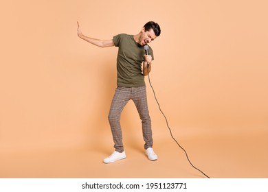 Full size photo of hooray brunet guy sing in mic wear t-shirt trousers sneakers isolated on beige color background - Shutterstock ID 1951123771