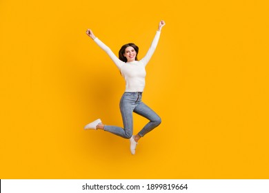Full size photo of hooray nice girl jump wear sweater jeans sneakers isolated on yellow color background