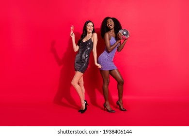 Full size photo of impressed brunette ladies with disco ball glass wear dress stilettos isolated on vibrant red color background
