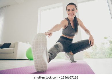 Full size photo of joyful active athlete girl want be strong sportswoman practice aerobics warm-ups sit on violet mat do squats stretch legs touch fingers foot in house like fitness studio
